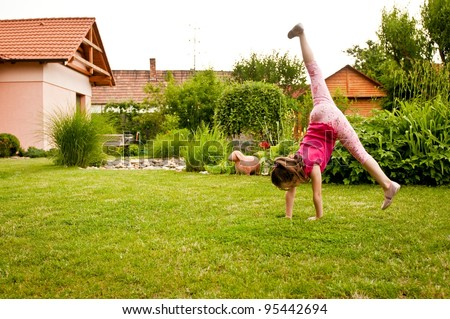 Child doing cartwheel in backyard