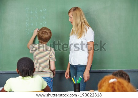 Child doing math in chalkboard in elementary school class