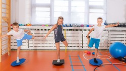 Child doing uni-pedal stance on a balancing disc during physical activity training, balance and coordination improvement