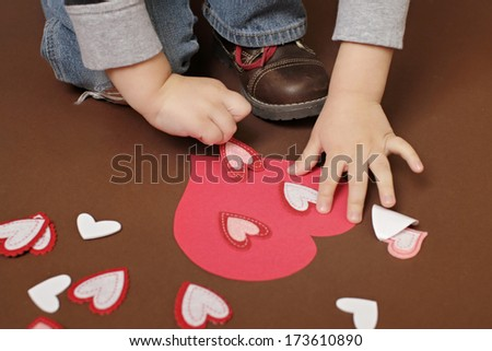 Child doing Valentine's Day Craft with Heart stickers