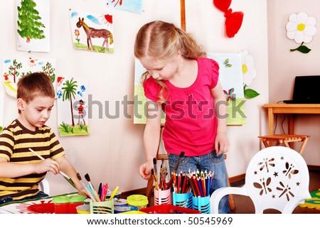 Child  draw paints in play room. Preschool.