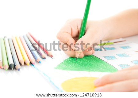 Child drawing a home with pencil