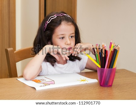 Child drawing a house and thinking