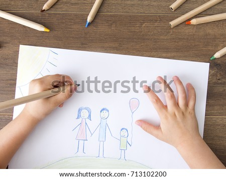 Child drawing happy family on paper. Top View #713102200