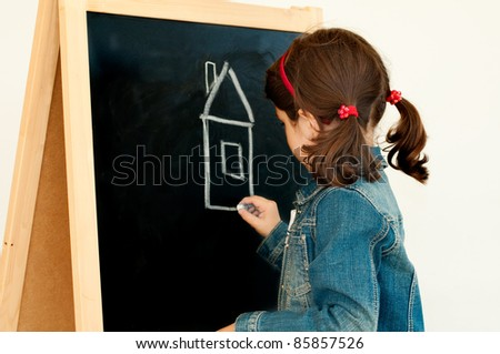 Child drawing house on a blackboard