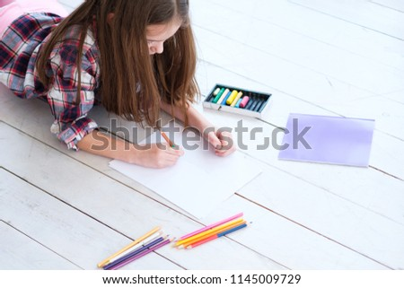 child drawing leisure. little girl lying on the floor and creating a picture with pencils.