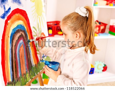 Child drawing on the easel at school.