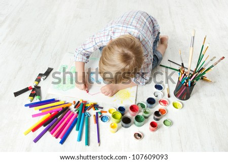 Child drawing picture with crayon  in album using a lot of painting tools. Creativity concept.