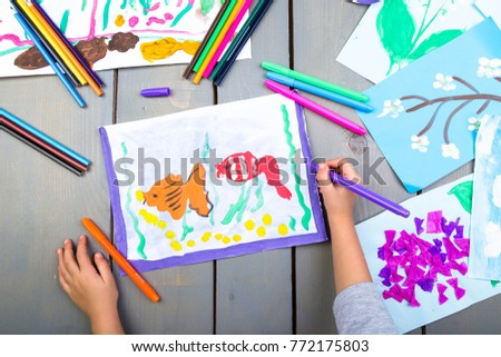 Child drawing. Top view of child hands with pencil painting picture on paper. Kid drawings