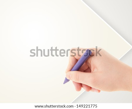 Child drawing with colorful crayon on empty plain blank paper