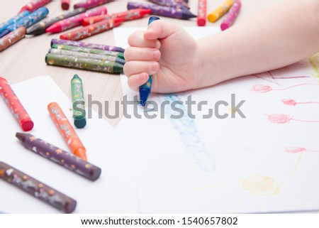 child draws a blue wax crayon cloud on paper