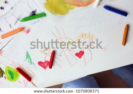 Child draws a pencil drawing of happy family.  #1070808371