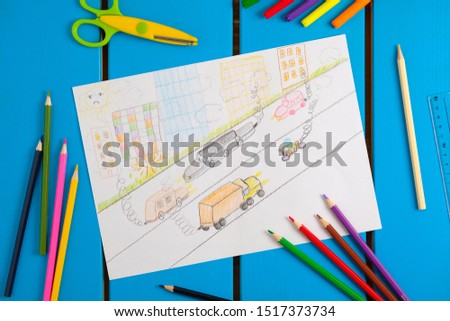 Child draws a pencil drawing of the city, cars and air pollution. Top view.