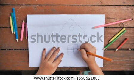 Child draws a pencil drawing of the house and his family. New home.