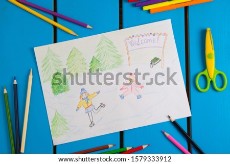 Child draws a pencil drawing the winter. Kids skate on the rink. Christmas tree, sleigh. Top view.