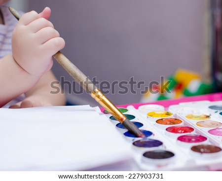 child draws a picture of the watercolor, the hand of a young child with a brush and paints closeup