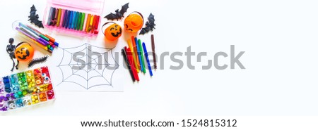 Child draws a rainbow cobweb. Drawing halloween Crayons and material for creativity. Autumn holiday. Copy space