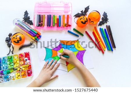 Child draws a rainbow cobweb. Drawing halloween Crayons and material for creativity. Autumn holiday.