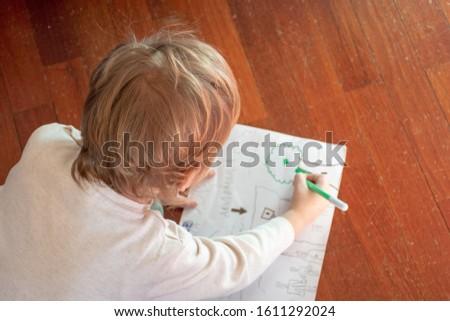 Child draws a tree on the floor