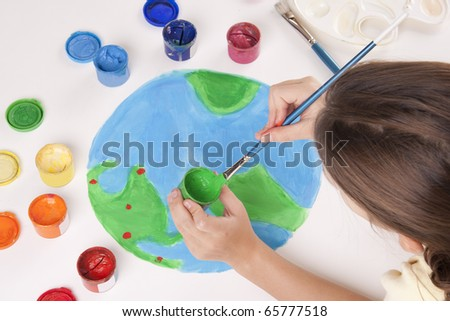 child draws colored paints globe