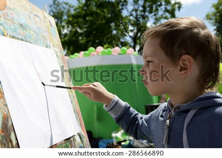 Child draws paints on the paper in the park