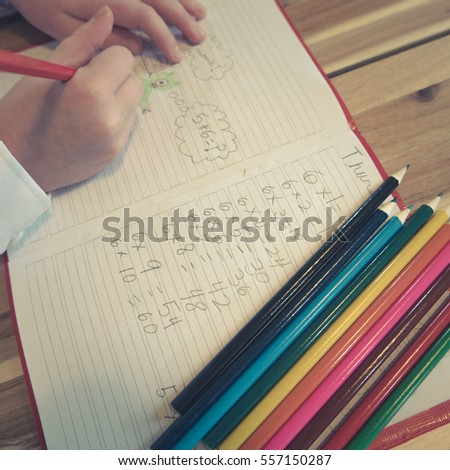 Child Draws Pictures In School Math Notebook
