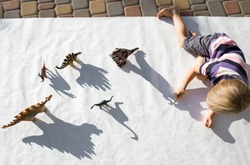 child draws with a pencil contrasting shadows from figures of toy dinosaurs on a light background. little scientist, ideas for the development of creative thinking, interesting activities for children