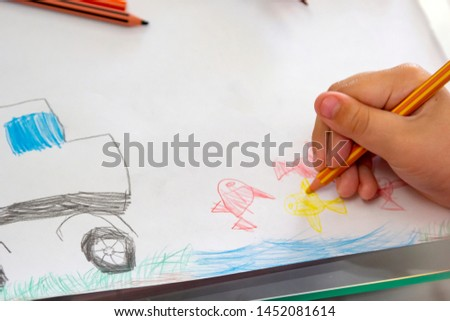 Child draws with colorful pencils. Children's drawing on theme of fishing with goldfish, car