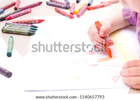 child draws with crayons on paper