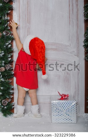 Child dressed as Santa with gift opens door for Christmas
