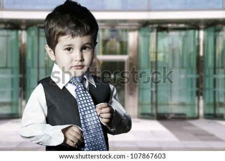 child dressed businessman smiling in front of building