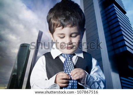 child dressed businessman with hands in his tie and skyscrapers in the background