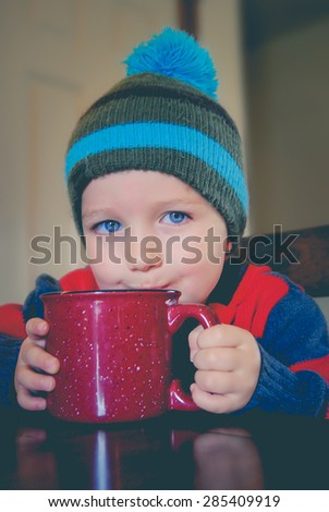 Child drinking hot chocolate from a mug.