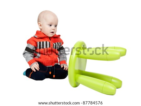 child dropped a plastic chair in the studio on a white background