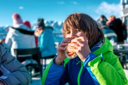 Child eating a steak with french fries in a refuge after skiing