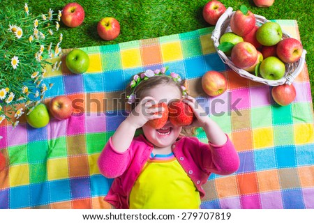 Child eating apple. Little girl playing peek a boo holding fresh ripe apples. Kids eating snack relaxing on a lawn. Children summer fun on a farm picking healthy fruit.