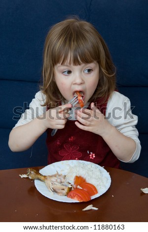 child eating chicken, rice and tomatoes for dinner