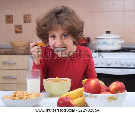 Child eating cornflakes on the kitchen