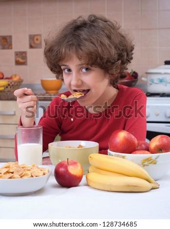 Child eating cornflakes on the kitchen - stock photo