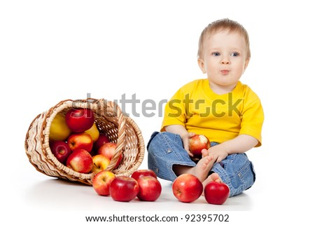 child eating red apples;  near basket