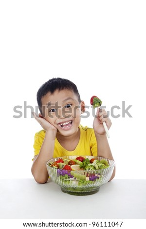 Child eating salad, shot in studio isolated on white background