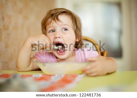 child eats cereal with spoon in home