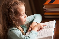 Child education. Girl reading book.