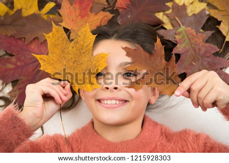 Child enjoy fall season. Girl cute kid lay on orange background with fallen leaves. Dry maple leaves in her hairstyle. Fall season concept. Hair care in autumn tips and ideas. Fall is on her mind.