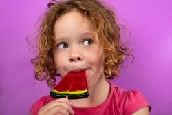 child enjoying watermelon lollipop, pretty little girl licking candy.