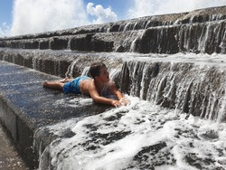 child enjoys overflowing ocean water on the steps of Bajamar, Tenerife