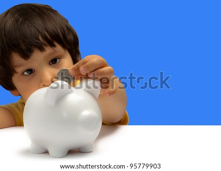 child entering a coin in a piggy bank
