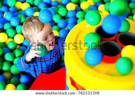 Child excited by playing with colorful balls in playing centre