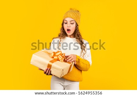 Child excited unpacking gift. Christmas present for daughter. Enjoy surprises. Kid little girl hold gift box with ribbon on yellow background. Teen girl received holiday gift. Best christmas gifts.