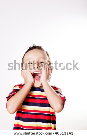 Child expressing surprise and happiness with his hands in his face